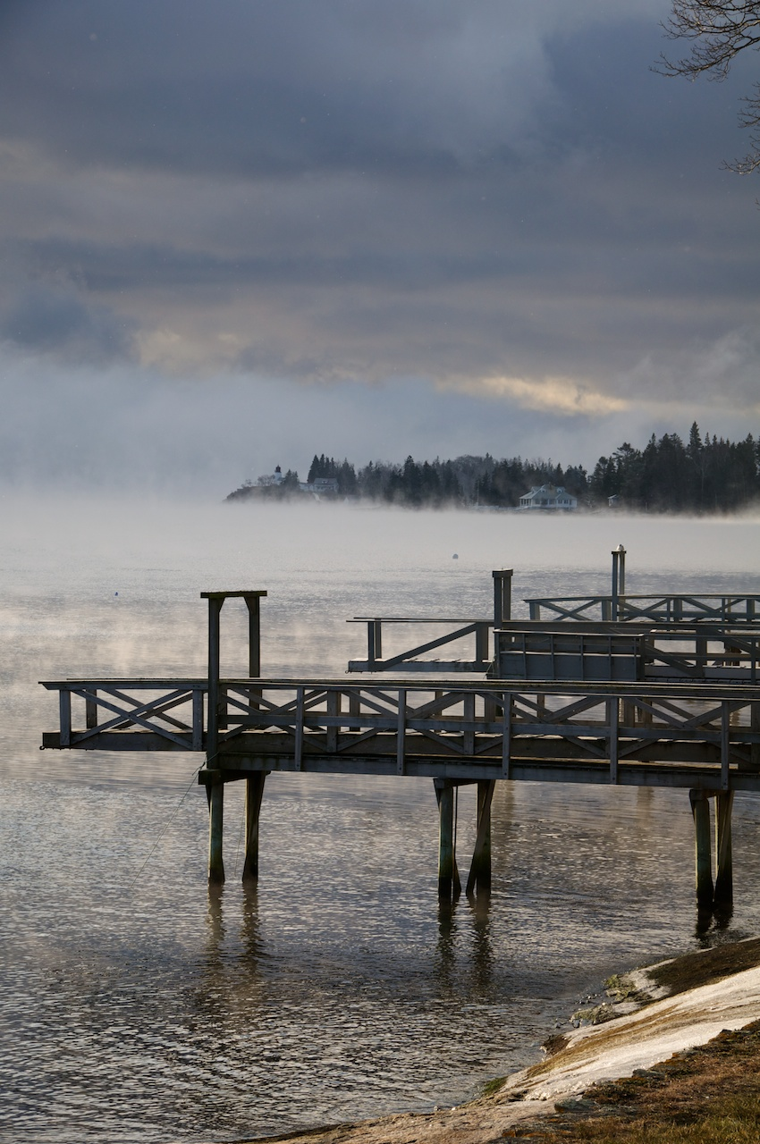 Three docks extending and Burnt Island in the sea smoke