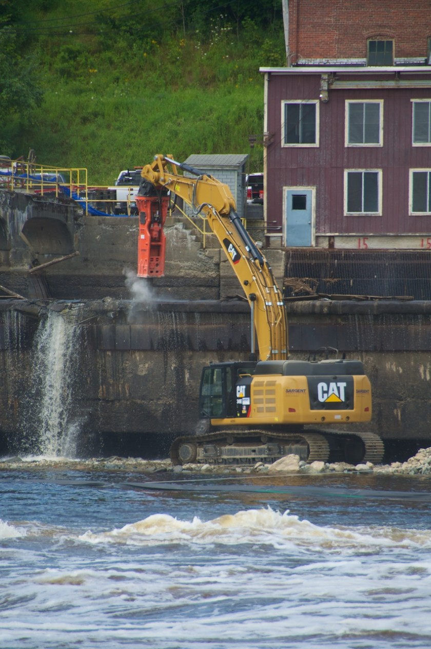 Excavators at work tearing down the Veazie Dam with the Shang-Tu Cabin.